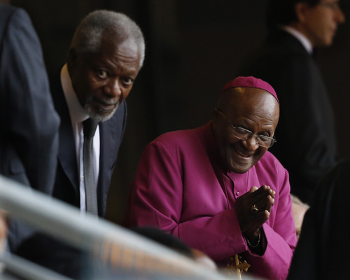 Retired Anglican Archbishop Desmond Tutu, right, arrives with Former U.N. Secretary-General Kofi Annan for the memorial service for former South African president Nelson Mandela at the FNB Stadium in Soweto near Johannesburg, Tuesday, Dec. 10, 2013. (AP Photo/Ben Curtis)