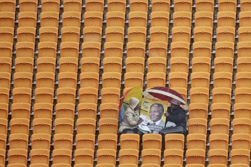 A couple sits under umbrellas in the rain and clean a poster of  former South Africa President Nelson Mandela with a towel before the memorial service for former South African president Nelson Mandela at the FNB Stadium in Soweto, near Johannesburg, South Africa, Tuesday Dec. 10, 2013. (AP Photo/Markus Schreiber)