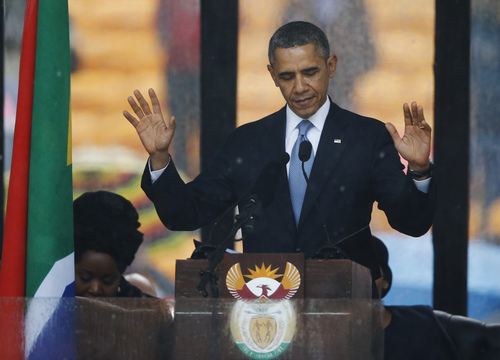 President Barrack Obama acknowledges applause before speaking at the memorial service for former South African president Nelson Mandela at the FNB Stadium in Soweto near Johannesburg, Tuesday, Dec. 10, 2013. (AP Photo/Matt Dunham)