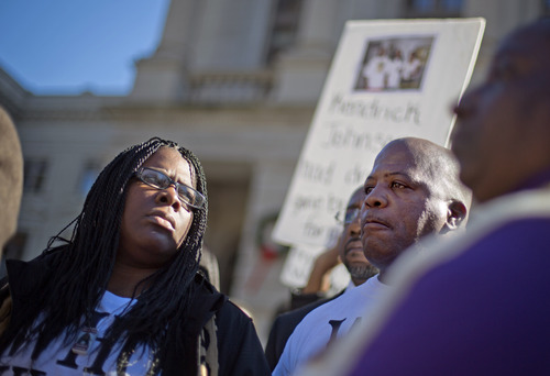 """Jacquelyn Johnson, left, stands next to her husband Kenneth, right, at a """"Who Killed K.J."""" rally in memory of their son, Kendrick Johnson, the south Georgia teenager found dead inside a rolled-up wrestling mat in his school, Wednesday, Dec. 11, 2013, in Atlanta. Lawyers for the parents of 17-year-old Kendrick Johnson are calling on the governor to order a coroner's inquest. The body of Johnson was found Jan. 11, and sheriff's investigators concluded that he died in a freak accident. (AP Photo/David Goldman)"""