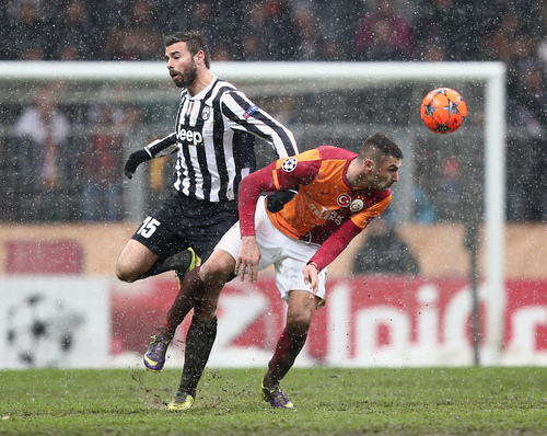 Galatasaray's Burak Yilmaz, right, and Andrea Barzagli of Juventus fight for the ball during their Champions League soccer match at the TT Arena Stadium in Istanbul, Turkey, Wednesday, Dec. 11, 2013. The match was halted Tuesday in the 31st minute with the score at 0-0 as hail and snow began to fall heavily in Istanbul, but resumed Wednesday. (AP Photo)