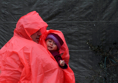 """A Syrian refugee man holds his son near his tent as a heavy snowstorm batters the region, in a camp for Syrians who fled their country's civil war, in the Chouf mountain town of Ketermaya, Lebanon, Wednesday, Dec. 11, 2013. The United Nations refugee agency says it is """"extremely concerned"""" for hundreds of thousands of Syrian refugees scattered across the region amid a snowstorm with high winds and torrential rains. (AP Photo/Mohammed Zaatari)"""