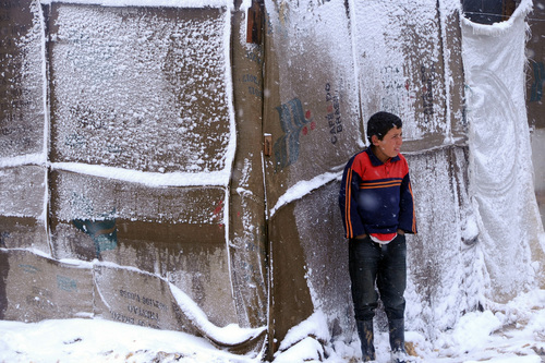 """A Syrian refugee boy stands outside his tent as a heavy snowstorm batters the region, in a camp for Syrians who fled their country's civil war, in the Bekaa valley, eastern Lebanon, Wednesday, Dec. 11, 2013. The United Nations refugee agency says it is """"extremely concerned"""" for hundreds of thousands of Syrian refugees scattered across the region amid a snowstorm with high winds and torrential rains. (AP Photo)"""
