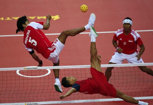 Indonesia's Nofrisal, left, returns a shot from Myanmar's Thant Zin Oo during the men's sepak takraw match at the South East Asian Games in Naypyitaw, Myanmar, Wednesday, Dec. 11, 2013. (AP Photo/Vincent Thian)