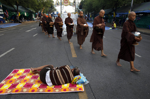 A group of Buddhist monks walk past a sleeping anti-government protester at a protest camp on a road near Government House, where Thai Prime Minister Yingluck Shinawatra's office is located, in Bangkok, Thailand early Wednesday, Dec. 11, 2013. (AP Photo/Greg Baker)