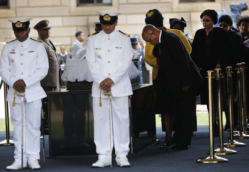 South African President Jacob Zuma pays his respects to former South African President Nelson Mandela during the lying in state at the Union Buildings in Pretoria, South Africa, Wednesday, Dec. 11, 2013. Second right is Mandela's widow Graca Machel and right, Winnie Madikizela-Mandela, Nelson Mandela's former wife. (AP Photo/Marco Longari, Pool)