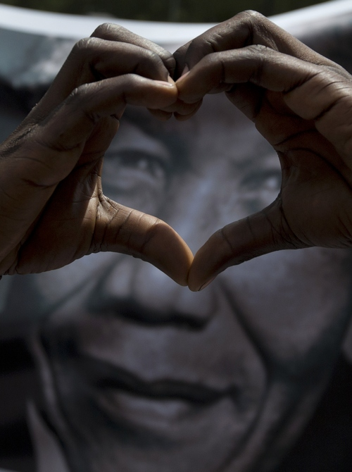 A man forms a heart when taking part in a march for former President Nelson Mandela outside the Union Buildings in Pretoria Wednesday Dec. 11, 2013, where the body of Mandela lies in state for three days. Each morning his remains will be transported from the mortuary to the government buildings. (AP Photo/Peter Dejong)
