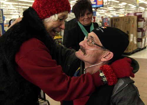 Leah Hogsten  |  The Salt Lake Tribune Former Ogden Salvation Army employee Douglas Holladay gets a hug from his mother Dorothy Holladay (left) and cousin Renay Camp (center)December 5, 2013, at the Riverdale Wal-Mart. Holladay was on a mission to fill three three red kettles with money for the needy. Holladay has terminal lung cancer and has been told by doctors that he may not live until Christmas, so he told The Salvation Army that he wanted to collect donations one final time.