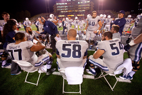 Utah State center Tyler Larsen, center, sits with his team on the sidelines during the first half of an NCAA college football game against New Mexico, Saturday, Oct. 19, 2013 in Albuquerque, N.M. Utah State won 45-10. (AP Photo/Eric Draper)