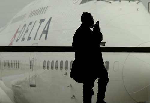 FILE - In this Oct. 29, 2012, file photo, a traveler on Delta Airlines waits for her flight in Detroit.  As federal regulators consider removing a decades-old prohibition on making phone calls on planes, a majority of air travelers oppose such a change, a new Associated Press poll finds on Wednesday, Dec. 11, 2013.  (AP Photo/Charlie Riedel, File)