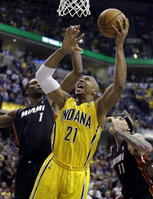 Miami Heat center Chris Bosh, left, fouls Indiana Pacers forward David West as he shoots in the second half of an NBA basketball game in Indianapolis, Tuesday, Dec. 10, 2013. The Pacers won 90-84. (AP Photo/Michael Conroy)