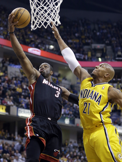 Miami Heat guard Dwyane Wade, left, shoots under Indiana Pacers forward David West in the first half of an NBA basketball game in Indianapolis, Tuesday, Dec. 10, 2013. (AP Photo/Michael Conroy)