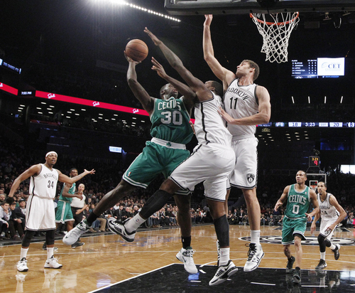 Brooklyn Nets Andray Blatche (0) and Brooklyn Nets Brook Lopez (11) defend Boston Celtics forward Brandon Bass (30) in the first half of their their NBA basketball game, Tuesday, Dec. 10, 2013, in New York. Brooklyn Nets forward Paul Pierce (34) gestures, far left. (AP Photo/Kathy Willens)