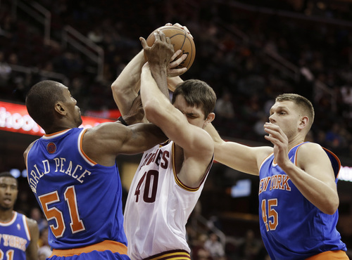New York Knicks' Metta World Peace (51) fouls Cleveland Cavaliers' Tyler Zeller (40) as Cole Aldrich (45) moves in in the fourth quarter of an NBA basketball game Tuesday, Dec. 10, 2013, in Cleveland. The Cavaliers won 109-94. (AP Photo/Mark Duncan)