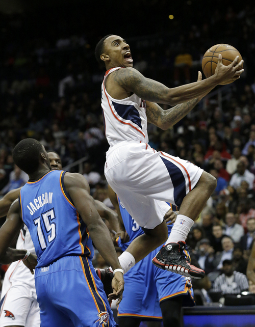 Atlanta Hawks point guard Jeff Teague, right, drives to the basket as Oklahoma City Thunder point guard Reggie Jackson (15) defends in the first half of an NBA  basketball game Tuesday, Dec. 10, 2013, in Atlanta. (AP Photo/John Bazemore)