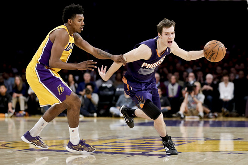 Los Angeles Lakers forward Nick Young, left, fouls Phoenix Suns guard Goran Dragic during the second half of an NBA basketball game in Los Angeles, Tuesday, Dec. 10, 2013. (AP Photo/Chris Carlson)