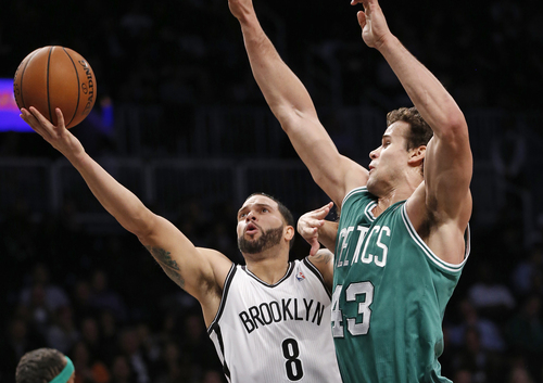 Brooklyn Nets guard Deron Williams (8) looks to shoot over the defense of Boston Celtics forward Kris Humphries (43) in the first half of their their NBA basketball game, Tuesday, Dec. 10, 2013, in New York. Williams, in his return from recurring ankle injuries, was the Nets high scorer with 25 points in the Nets 104-96 victory over the Boston Celtics. (AP Photo/Kathy Willens)