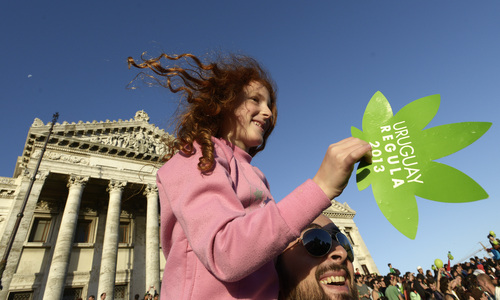 People attend a demonstration in support of the legalization of marijuana outside the Congress in Montevideo, Uruguay, Tuesday, Dec. 10, 2013. Uruguay's Senate was finishing its final debate Tuesday before voting on a plan to create the world's first national marijuana market, with the state regulating the entire process of growing, selling and using a drug that is illegal almost everywhere else. (AP Photo/Matilde Campodonico)