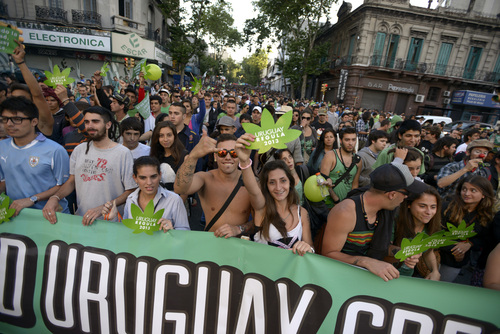 People attend a demonstration in support of the legalization of marijuana in Montevideo, Uruguay, Tuesday, Dec. 10, 2013. Uruguay's Senate was finishing its final debate Tuesday before voting on a plan to create the world's first national marijuana market, with the state regulating the entire process of growing, selling and using a drug that is illegal almost everywhere else. (AP Photo/Matilde Campodonico)