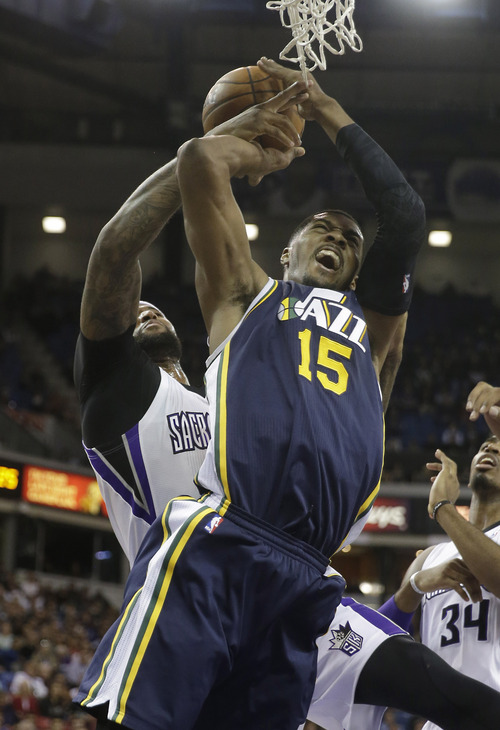 Utah Jazz forward Derrick Favors, right, is fouled by Sacramento Kings center DeMarcus Cousins during the first quarter of an NBA basketball game in Sacramento, Calif., Wednesday, Dec. 11, 2013. (AP Photo/Rich Pedroncelli)