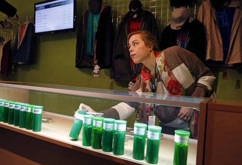 In this Dec. 6, 2013 photo, Elle Beau, an employee of The Clinic, a Denver-based dispensary with several outlets, reaches into a display case for marijuana while helping a customer, in Denver. The Clinic is among the roughly 150 medical marijuana dispensaries hoping to begin selling to recreational users when it becomes legal to sell on Jan. 1, 2014. The state's hopeful pot shops are so mired in red tape and confusion that no one knows yet when or if they'll be allowed to open. Not a single shop will clear state and local licensing requirements until about Dec. 27. (AP Photo/Brennan Linsley)(AP Photo/Brennan Linsley)