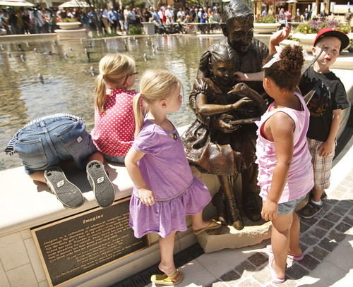 "Leah Hogsten  |  The Salt Lake Tribune The multimillion-dollar, 5,000-square-foot fountain features six fine-art bronze statues, created by sculptor Brian Keith that were dedicated Friday, June 15, 2012 in Farmington. Children play on one of the scuptures titled ""Imagine."" The Station Park shopping center in Farmington unveiled a world-class show fountain with choreographed lights, music, color and 30-60-foot high dancing water."