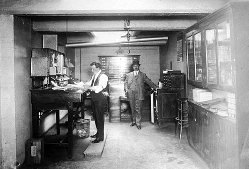 Photo Courtesy Utah State Historical Society  Image shows two men standing in the office of the Gray News Company in 1911.