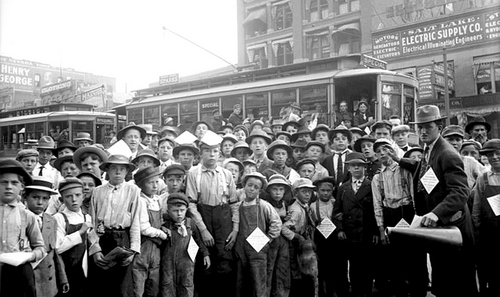 Photo Courtesy Utah State Historical Society  Image shows a large crowd of paperboys on Main Street in front of the Salt Lake Telegram building in 1910.