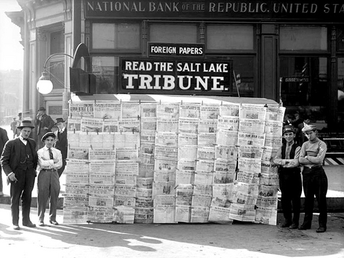 Photo Courtesy Utah State Historical Society  Paperboys standing on either side of a newspaper cart, selling the Salt Lake Tribune in 1914.