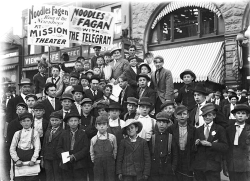"""A group of newboys stand outside the Tribune Building in 1910, waiting for Noodles Fagan. Lawrence C. """"Noodles"""" Fagan, formerly a newsboy and by then a vaudeville comedian, founded the organization that eventually became Local 404 of the Non-Conformists Union. At the time, Mr. Fagan's new organization was then known as The Fraternal Order of Nonconformists, International. Courtesy Utah State Historical Society"""