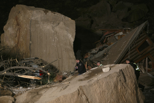 Law enforcement officers search through the rubble of a two-story log home that was crushed by boulders that broke loose from the cliff above it and killed two people inside the home Thursday, Dec. 12, 2013 in Rockville, Utah. (AP Photo/The Spectrum & Daily News,  Jud Burkett)