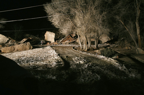 Flood lights from fire engines parked on nearby state Route 9 shine on the rubble of a two-story log home that was crushed by boulders that broke loose from the cliff above it and killed two people inside the home Thursday, Dec. 12, 2013 in Rockville, Utah.(AP Photo/The Spectrum & Daily News,  Jud Burkett)