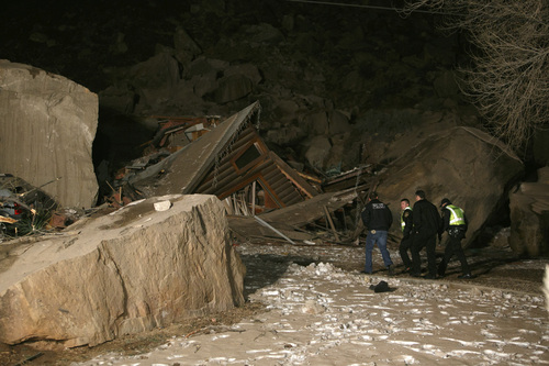 Law enforcement officers search through the rubble of a home that was crushed by boulders that broke loose from the cliff above it and killed two people inside the home Thursday, Dec. 12, 2013 in Rockville, Utah. (AP Photo/The Spectrum & Daily News,  Jud Burkett)