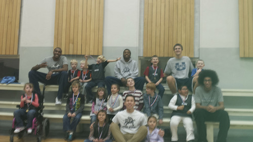 Courtesy Erica Lundahl Utah State basketball players (from left) Jarred Shaw, Jojo McGlaston, Viko Noma'aea, Carson Shanks and Jalen Moore pose with kids from Top Sports. Several Aggies took time Dec. 11 to assist the program, which allows kids with disabilities to participate in athletics.