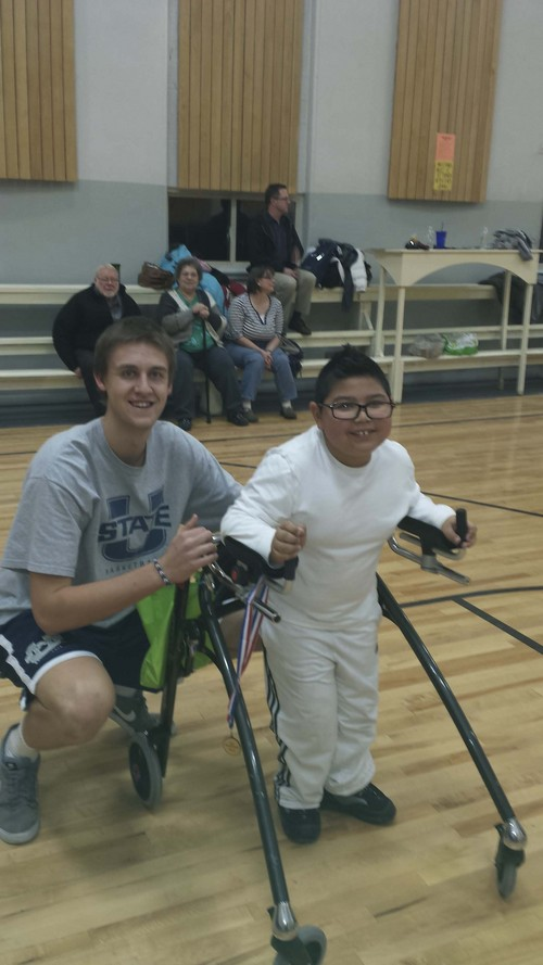 Courtesy Erica Lundahl Seven-foot Utah State freshman Carson Shanks bends down for a picture with Dillon Lundahl, a participant in Top Sports. Several Aggies took time Dec. 11 to assist the program, which allows kids with disabilities to participate in athletics.