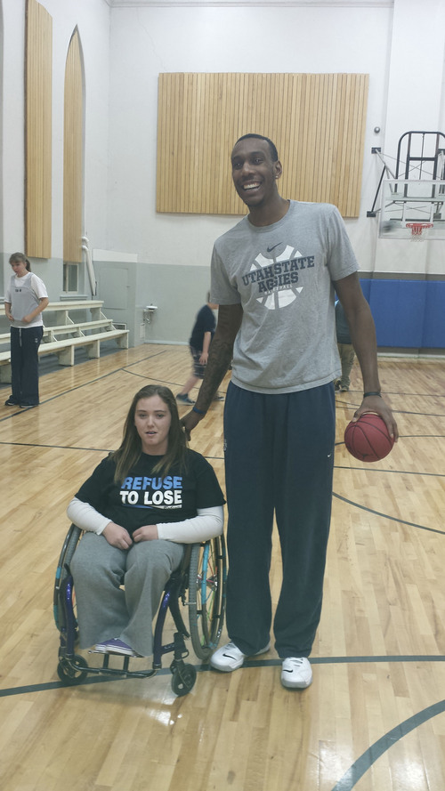 Courtesy Erica Lundahl Senior Utah State center Jarred Shaw poses with Brooklyn Godderidge, a participant in Top Sports. Several Aggies took time Dec. 11 to assist the program, which allows kids with disabilities to participate in athletics.