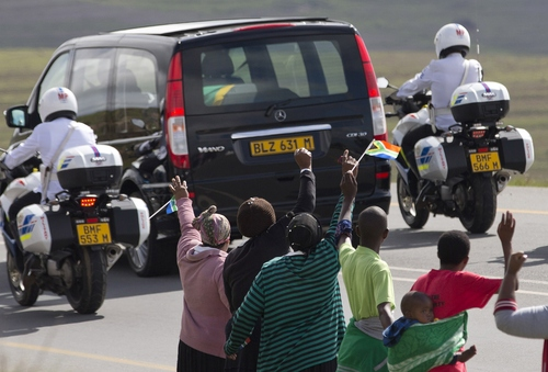People wave goodbye as the funeral procession carrying the remains of former South African President Nelson Mandela proceeds to Mandela's hometown and burial site in Qunu, South Africa, Saturday Dec. 14, 2013. The iconic leader will be buried on Sunday close to his house. (AP Photo/Peter Dejong)