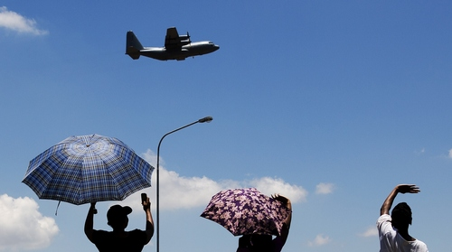 People wave at an aircraft carrying the casket of former South African President Nelson Mandela as it takes off from Waterkloof Air Base on the outskirts of Pretoria, South Africa, Saturday, Dec. 14, 2013.  On a final journey to his home village where he had wanted to spend his final days, the remains of Nelson Mandela were honored amid pomp and ceremony Saturday at an air base in South Africa's capital before being loaded onto a plane.  (AP Photo/Matt Dunham)
