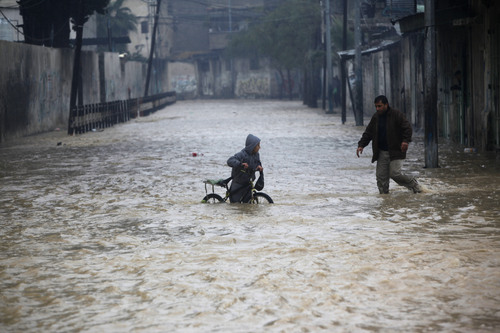 A Palestinian man helps a boy out of a flooded street following heavy rains in Gaza City, Saturday, Dec. 14, 2013. Hundreds of houses were flooded following a rain storm in Gaza. Rescue workers evacuated more than 5,000 Gaza Strip residents from homes flooded by four days of heavy rain, using fishing boats and heavy construction equipment to pluck some of those trapped from upper floors, an official said Saturday. (AP Photo/Adel Hana)