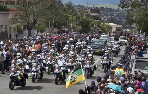 The motorcade transporting the body of Nelson Mandela, in black hearse, passes through crowds of mourners gathered in the town of Umtatha on its way to Qunu, South Africa Saturday, Dec. 14, 2013. (AP Photo/Ben Curtis)