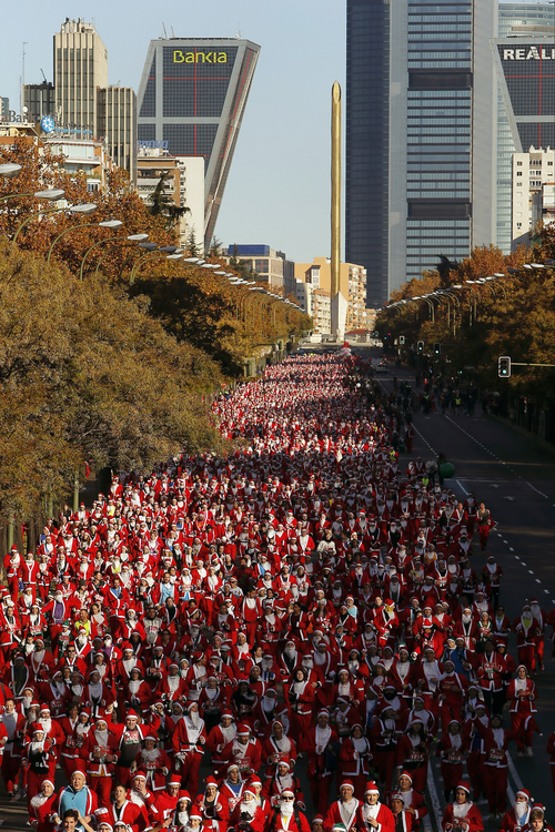 """Revelers dressed as Santa Claus run during a Marathon in Madrid, Spain, Saturday, Dec. 14, 2013. Around 6,000 people dressed as Santa Claus and his elves have run a """"mini-marathon"""" through the streets of Madrid to promote festive cheer as the country tries to emerge from a two-year recession. While grown-ups dressed in red costumes with wispy white beards, children donned green elf outfits to run the 5.5 kilometer (3.4 miles) course through the city center. The race was organized Saturday by one of Spain's leading department stores and it contributed 1 euro ($1.34) for each entrant to a charity that buys Christmas presents for deprived children around the world. (AP Photo/Andres Kudacki)"""