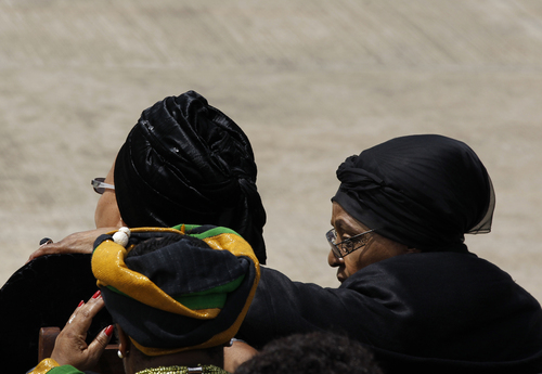 Winnie Madikizela-Mandela, right, Nelson Mandela's former wife, puts her around Nelson Mandela's widow Graca Machel as they wait for the arrival of the former South African president's casket at the Mthatha airport in the Eastern Cape province of South Africa, December 14, 2013. (AP Photo/Siphiwe Sibeko, Pool)