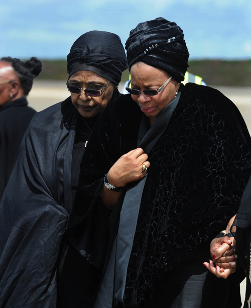Former South African President Nelson Mandela's widow Graca Machel, right, and Winnie Madikizela-Mandela, Nelson Mandela's former wife, walk together before the arrival of the former president's casket arrives at Mthatha Airport in Mthatha, South Africa, Saturday, Dec. 14, 2013. The funeral service for Nelson Mandela will be held in his home town of Qunu on Sunday. (AP Photo/Kopano_Tlape, CGIS)