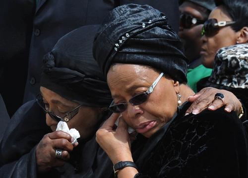 Former South African President Nelson Mandela's widow Graca Machel, right, and Winnie Madikizela-Mandela, Nelson Mandela's former wife, wipe their tears as the former president's casket arrives at Mthatha Airport in Mthatha, South Africa, Saturday, Dec. 14, 2013. The funeral service for Nelson Mandela will be held in his home town of Qunu on Sunday. (AP Photo/Kopano_Tlape, CGIS)