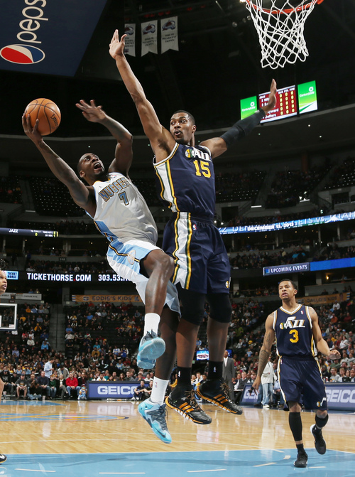 Denver Nuggets forward J.J. Hickson, front left, is fouled as he goes up for a shot by Utah Jazz center Derrick Favors, front right, as Jazz guard Trey Burke trails the play in the first quarter of an NBA basketball game in Denver on Friday, Dec. 13, 2013. (AP Photo/David Zalubowski)