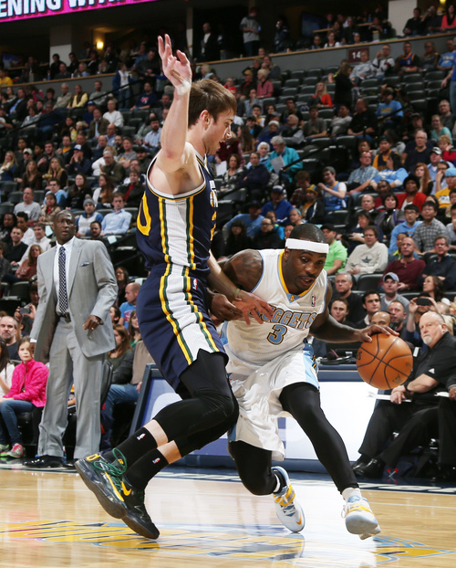 Denver Nuggets guard Ty Lawson, right, works the ball inside for shot as Utah Jazz guard Gordon Hayward covers in the first quarter of an NBA basketball game in Denver on Friday, Dec. 13, 2013. (AP Photo/David Zalubowski)