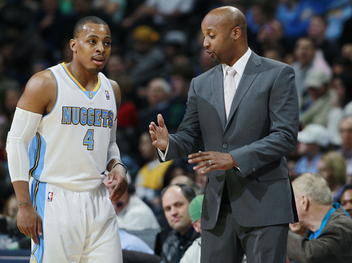 Denver Nuggets head coach Brian Shaw, right, confers with guard Randy Foye during a break against the Utah Jazz in the first quarter of an NBA basketball game in Denver on Friday, Dec. 13, 2013. (AP Photo/David Zalubowski)