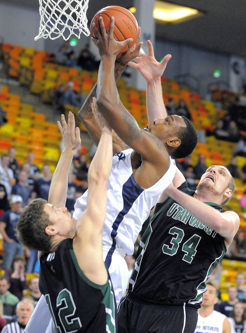 Utah State's Jarred Shaw, center, grabs a rebound over Utah Valley's Holton Hunsaker (12) and Ben Aird (34) during an NCAA college basketball game, Saturday, Dec. 14, 2013, in Logan, Utah. (AP Photo/The Herald Journal, Eli Lucero)