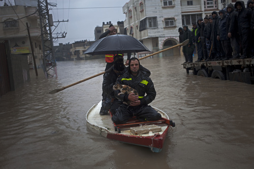 Palestinian rescue members evacuate a cat following heavy rains in Gaza City, Saturday, Dec. 14, 2013. Rescue workers evacuated more than 5,000 Gaza Strip residents from homes flooded by four days of heavy rain, using fishing boats and heavy construction equipment to pluck some of those trapped from upper floors, an official said Saturday. (AP Photo/Khalil Hamra)
