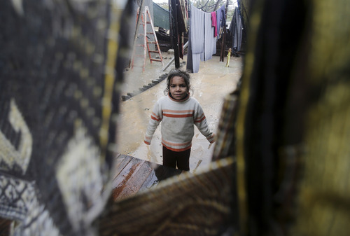 A Palestinian girl looks through a destroyed family house during heavy rains in Gaza City, Saturday, Dec. 14, 2013. Rescue workers evacuated more than 5,000 Gaza Strip residents from homes flooded by four days of heavy rain, using fishing boats and heavy construction equipment to pluck some of those trapped from upper floors, an official said Saturday. (AP Photo/Adel Hana)